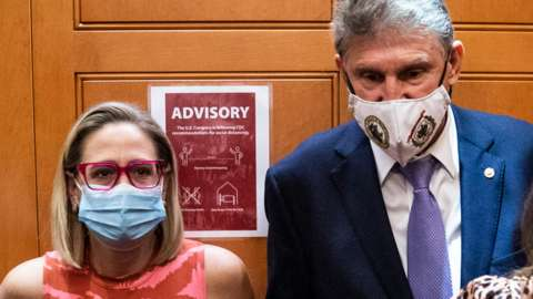 Sen. Kyrsten Sinema and Sen. Joe Manchin board an elevator on Capitol Hill on 30 Sept 2021 in Washington, DC
