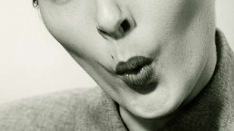 Greyscale close up image of woman whistling