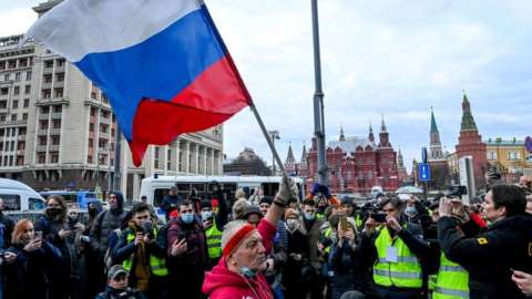 An opposition supporter waves a Russian national flag during a rally