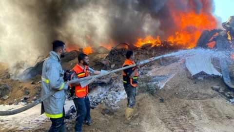 Palestinian firefighters put out a fire at building hit by Israeli strikes in southern Gaza