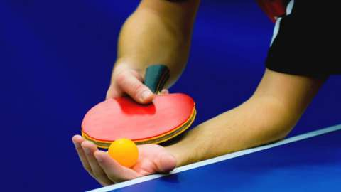 Hand holding table tennis bat and ball. File photo