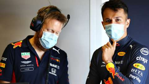 Alex Albon and a Red Bull engineer wear face masks
