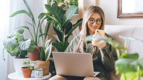 Woman looking happy working on a laptop surrounded by plants