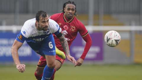 Andrew Boyce of Eastleigh heads the ball clear