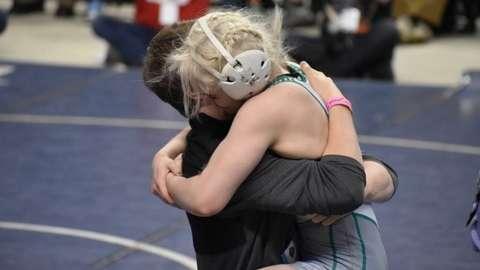 A teenage girl dressed in amateur wrestling gear hugging an older man