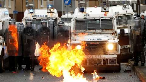 PSNI officers in riot gear and Land Rovers as a fire burns on the Springfield Road, Belfast 8 April 2021
