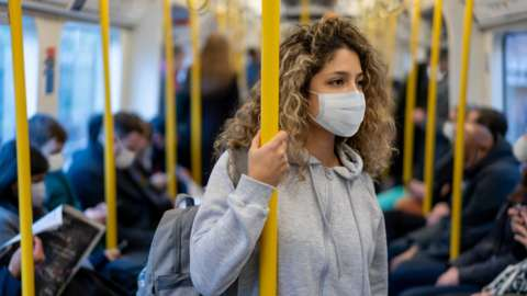 Woman on a train in a mask