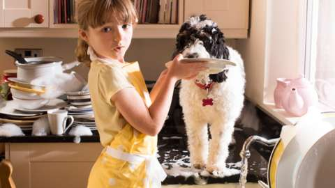 Little girl and pet dog help with the dishes