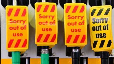 """An """"out of use"""" sign covers fuel pumps at a petrol station in Birkenhead, northwest England on September 27, 2021"""