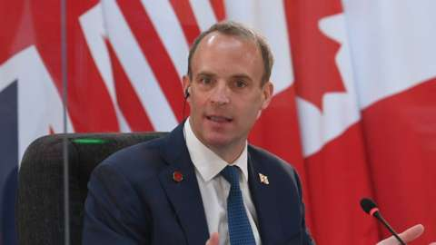 Dominic Raab delivers an address seatd before a range of flags