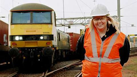 Heather Waugh, stands in front of a Class 90 locomotive, at the start of her shift