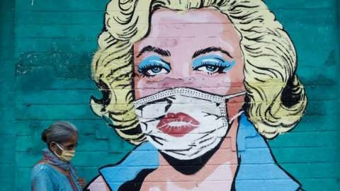 A woman wearing a protective mask walks past a graffiti depicting former American actress Marilyn Monroe wearing a mask, amidst the spread of the coronavirus disease (COVID-19), on a street in Mumbai, India, March 30, 2021.