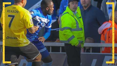 Jai Reason of Dover Athletic holds back Hartlepool United's Gus Mafuta following abuse from the crowd
