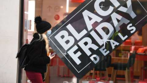Woman walks past Black Friday promotion sign