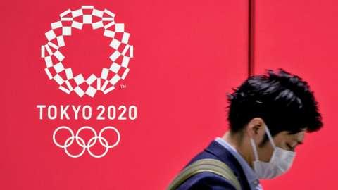 A man walks past a Tokyo 2020 advertising poster at the Shinjuku Metro Station, in Shinjuku area of Tokyo