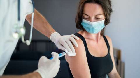 A woman in a mask being injected in the arm looks down at the syringe being held by a masked hand