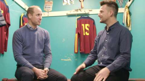 Prince William talks to Matthew in a football changing room