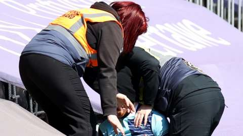 Swansea stewards remove a fan wearing a Wycombe Wanderers shirt from Liberty Stadium