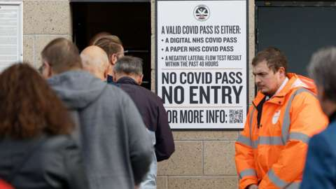people queue into football stadium by sign reading 'no covid pass, no entry'