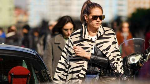 A guest wears earrings, sunglasses, a beige and black zebra pattern jacket, a black leather jacket, outside MSGM, during Milan Fashion Week