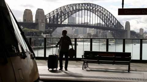 Silhouetted picture of a masked passenger on a train platform in front of the Sydney Harbour Bridge
