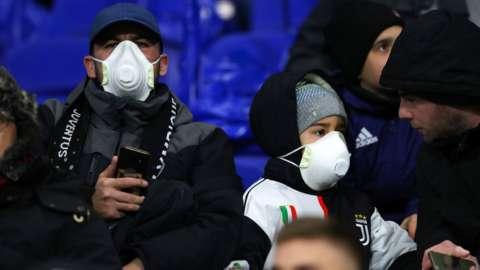 Two Juventus supporters wearing face masks to guard against coronavirus