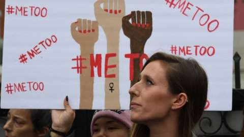 protesters hold metoo signs