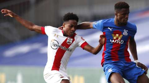 Wilfried Zaha of Crystal Palace is challenged by Kyle Walker-Peters