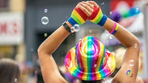 A woman wears a rainbow hat and wristbands at a Pride event