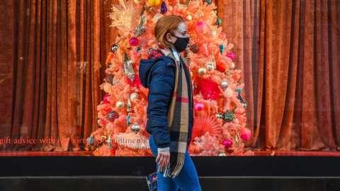 woman walking past Christmas tree