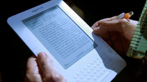 A white Amazon Kindle 2 is held by a person next to a pen and notepad