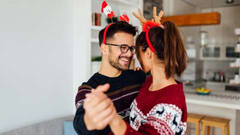 Couple dancing with Christmas jumpers on