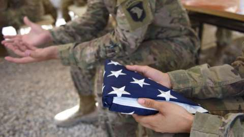 A US soldier holds the national flag ahead of a handover ceremony at Leatherneck Camp in Lashkar Gah in the Afghan province of Helmand