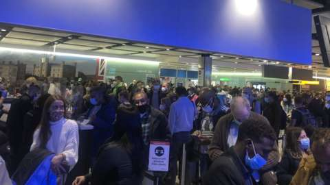 Large queue of travellers at Heathrow Airport