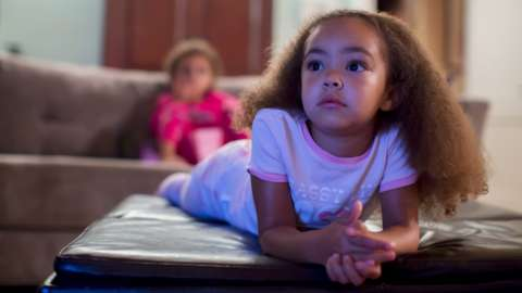 A young girl watching TV