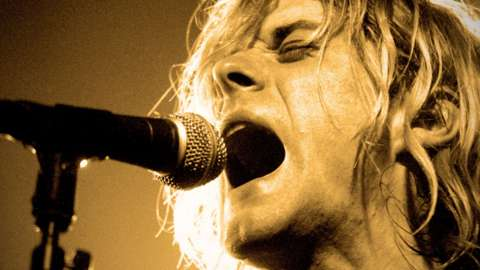 Kurt Cobain of Nirvana singing into a microphone