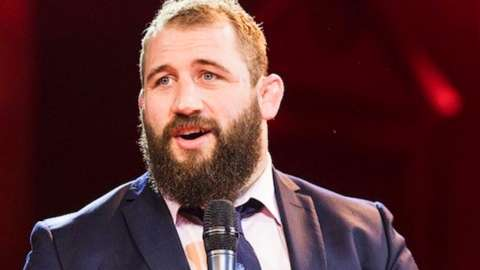 Rugby player Joe Marler wearing a black suit and tie, holding a microphone