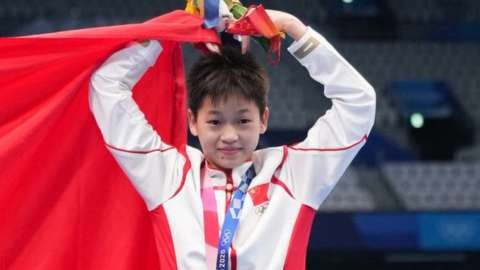 Gold medalist Quan Hongchan of China poses with a Chinese national flag during the medal ceremony for the Women's 10m Platform Final