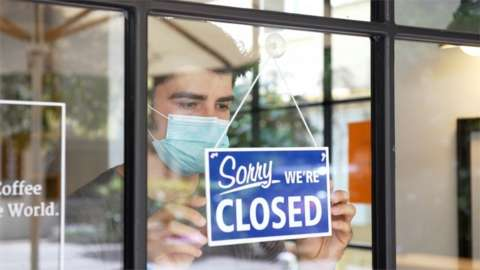 Man with mask putting closed sign on shop window