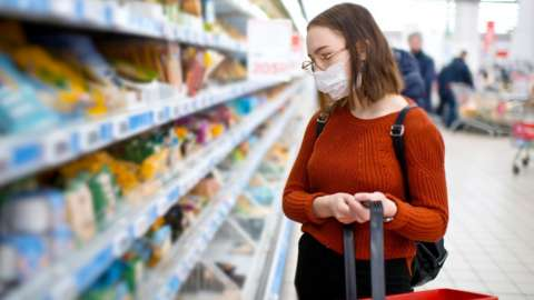 A woman wearing a facemask in a supermarket