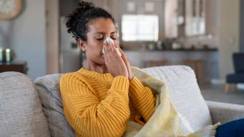 young black woman sneezing in to tissue at home