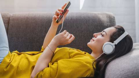 A woman listening to music using headphone (stock image)
