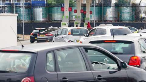 Cars queue at a petrol station forecourt