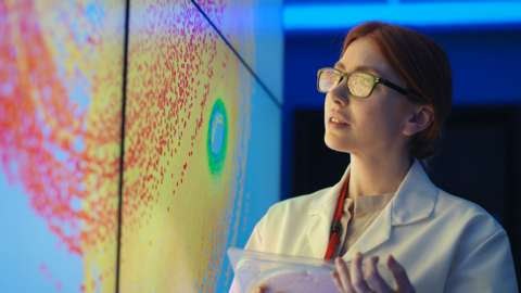 A female scientist looking at a display screen