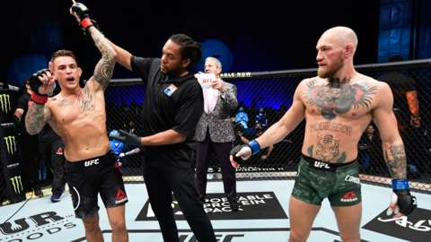 Poirier is given victory while McGregor stands beside him