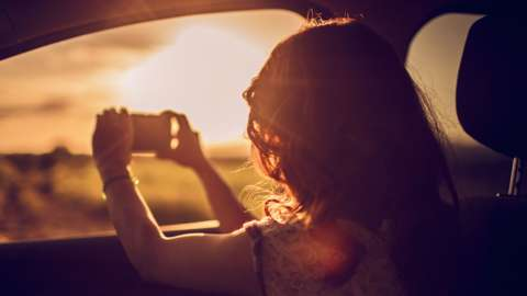 Woman photographing a sunrise