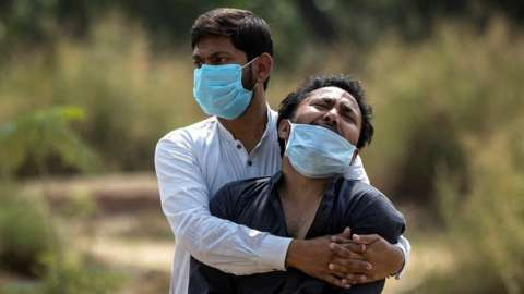 A man is consoled by his relative as he sees the body of his father, who died from the coronavirus disease (COVID-19), before his burial at a graveyard in New Delhi, India, April 16, 2021.