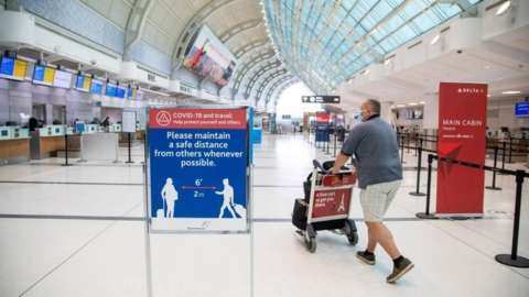 A man pushes a cart at an airport in Toronto