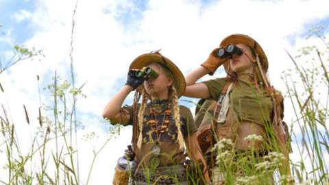 Two young girls dressed as explorers look through binoculars