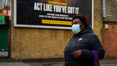 A pedestrian wearing a face covering walks past a coronavirus information poster in Manchester in February 2020